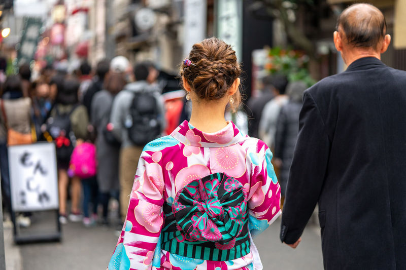 Rear View Adult City Women Street Men Incidental People Real People People Focus On Foreground Lifestyles Clothing Day Standing Waist Up Walking Two People Architecture Casual Clothing Leisure Activity Hairstyle
