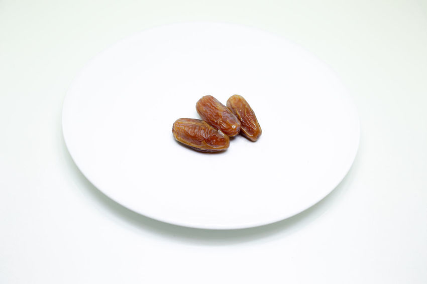Dates on white plate Close-up Day Food Food And Drink Freshness Healthy Eating Islamic No People Plate Rain Ramadhan Studio Shot White White Background