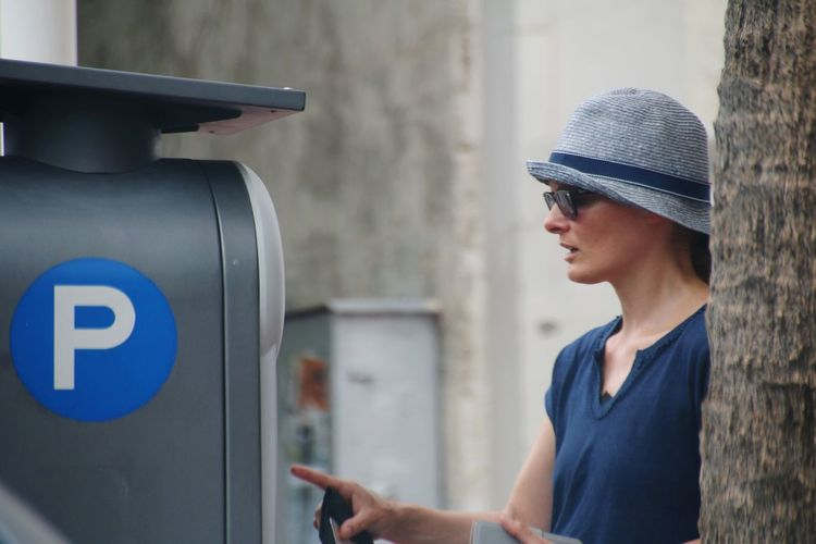 Midsection of woman wearing hat at atm