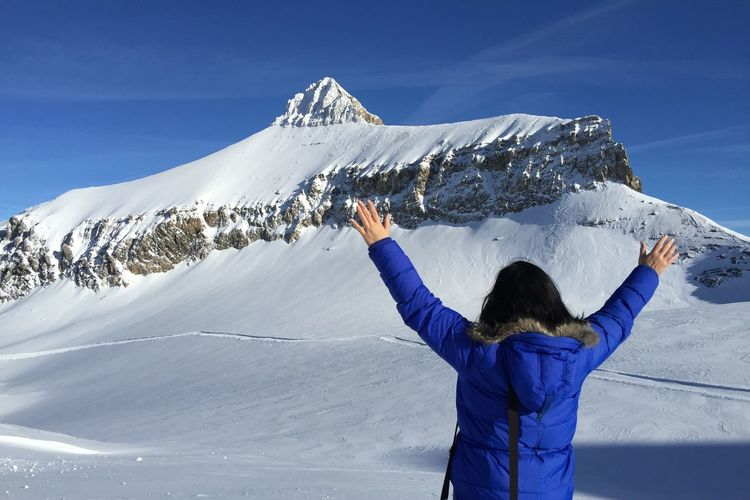 Rear view of woman on snowcapped mountain against blue sky