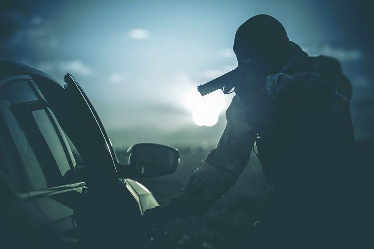 Male burglar hijacking car at night