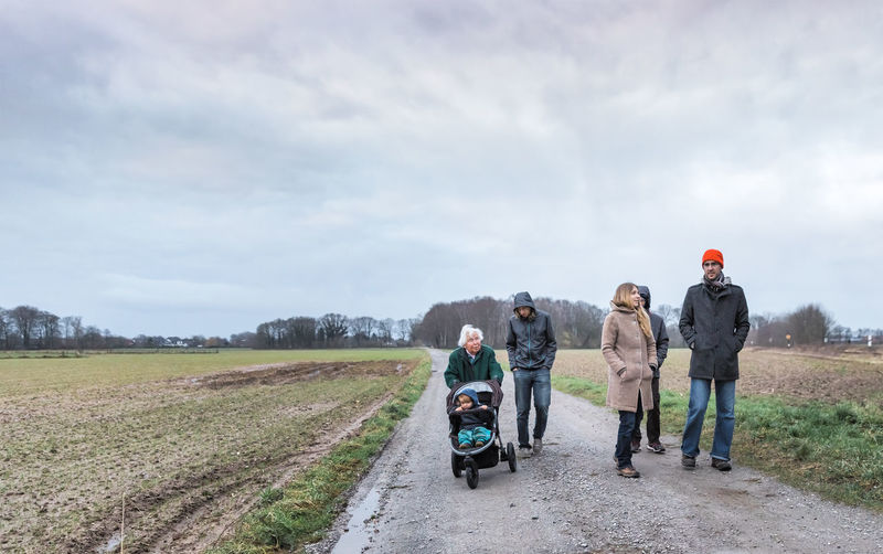 Family walking on dirt road amidst field