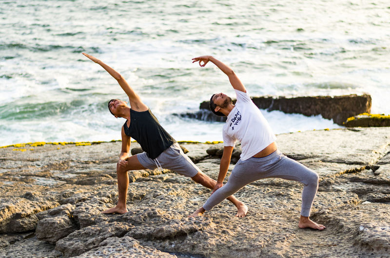 Full length of male friends doing yoga on rock at beach