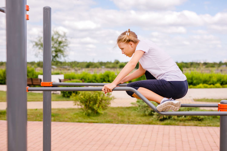 Side view of young woman holding railing