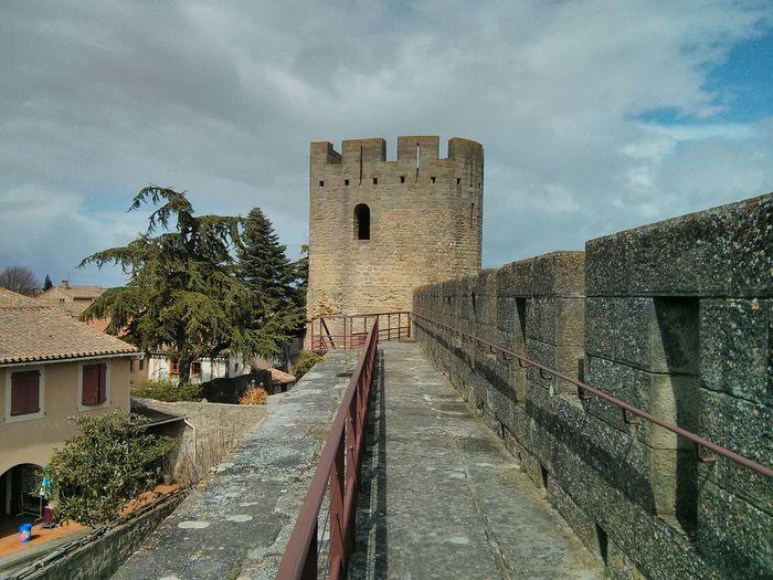 Walkway Leading Towards Castle Against Cloudy Sky