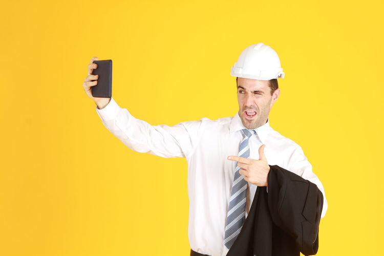 Man holding camera while standing against yellow background