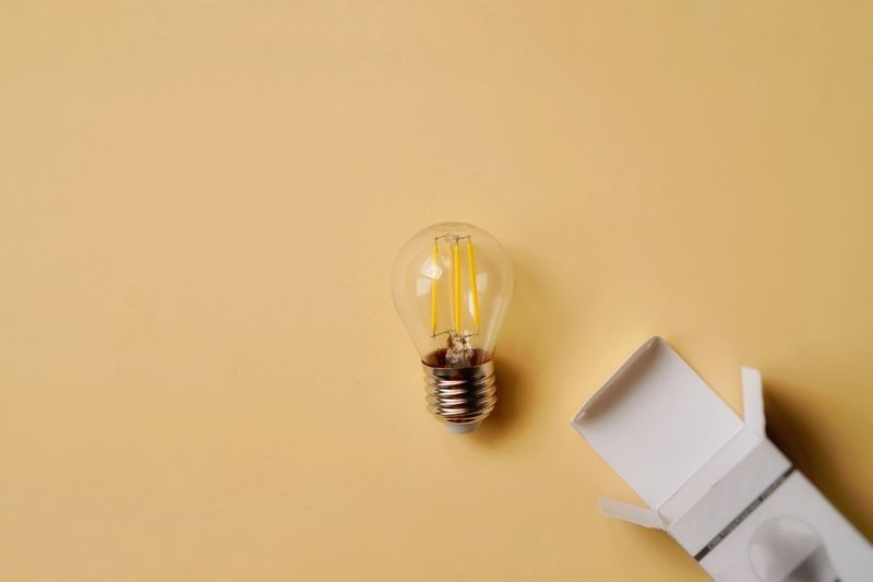 High angle view of light bulb on table against wall