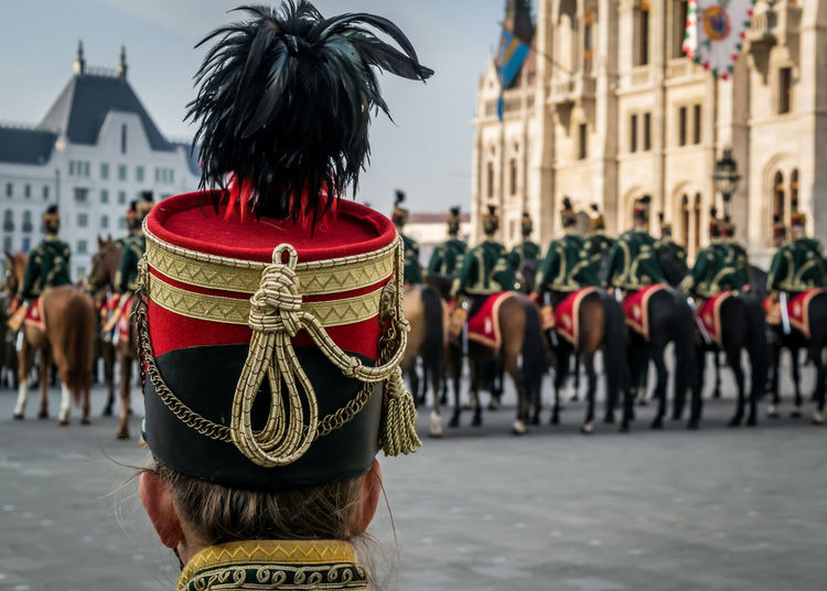 Hussar traditional military hat closeup. Background with line up of hussar cavalry on horses in front of the Parliament House during the 15 March military parade in Budapest, Hungary. Hungarian National Holiday. 15 March Budapest Hat Holiday Horses Hungary National Uniform Architecture Background Cavalry Closeup Costume Cultures Day History House Hungarian Hussar Military Parliament People Person Red Traditional Fresh On Market 2018