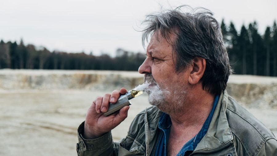 Man smoking electric cigarette outdoors
