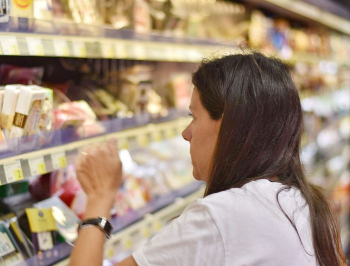 Woman looking at objects on shelf in super market