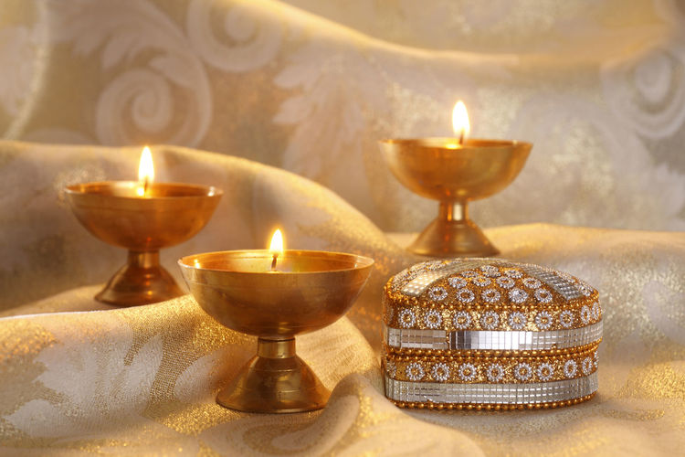 Close-Up Of Oil Lamps And Box On Fabric