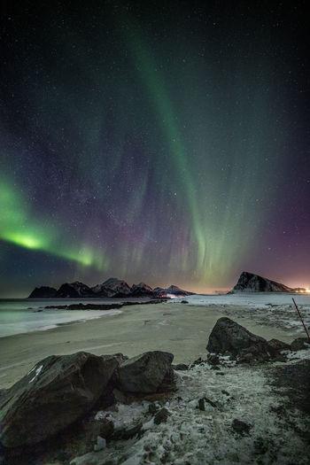 Scenic view of aurora polaris below beach against sky at night