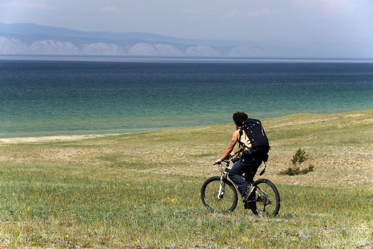 Man cycling on field against river