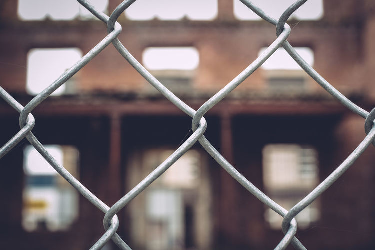 View of building seen through chainlink fence