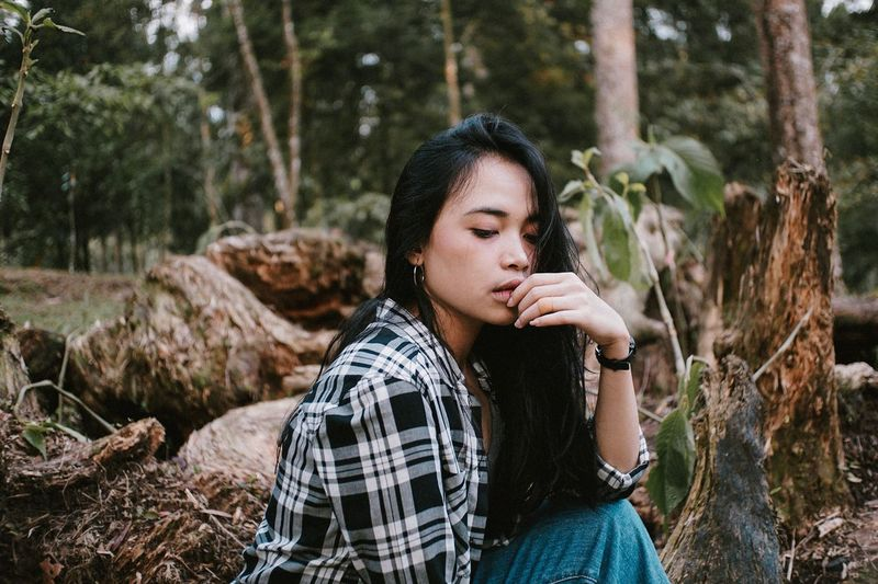 Young woman looking away while sitting on land in forest