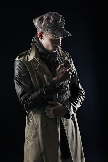 Studio photography. Three quarters portrait of a man in a leather cloak and cap. She smokes a pipe. Pensive. Like Sherlock Holmes. People Watching Portraits Studio Adult Black Background Clothing Cut Out Hat Indoors  Jacket Leather Looking Males  Men Mid Adult One Person People Portrait Portrait Photography Spy Standing Studio Shot Three Quarter Length Waist Up Young Adult