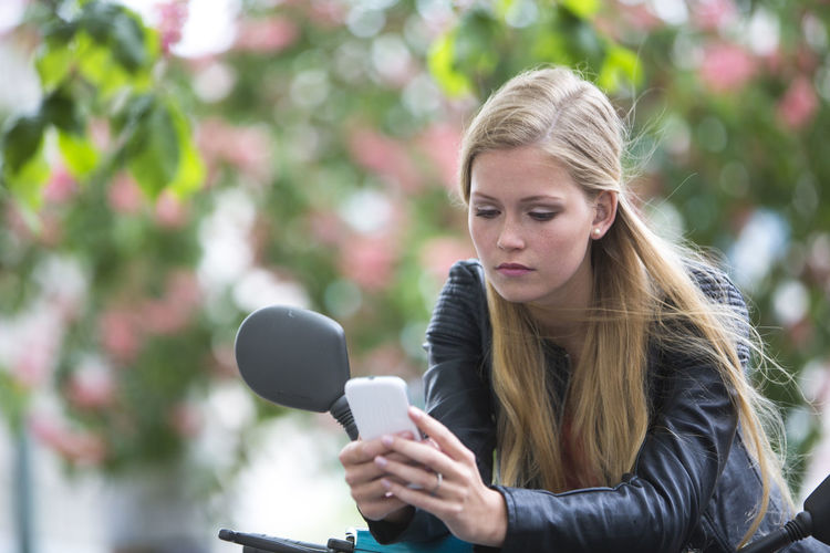 Transport Wireless Communication Using Phone Device Telephone Transportation Portrait Of A Woman Cute Real People Blond Hair Moped Young Woman Vespa Scooter Beautiful People Female Long Hair Attractive One Person Young Women Sad Texting Chatting Messaging Woman Portrait