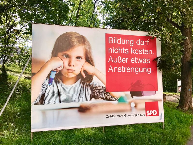 Billboard for the German Parliamentary Elections by the socialist party SPD. Text Tree One Person Outdoors Day Grass Nature Young Adult People Party Socialist Party Parliamentary Elections Spd Germany Politics And Government Politics
