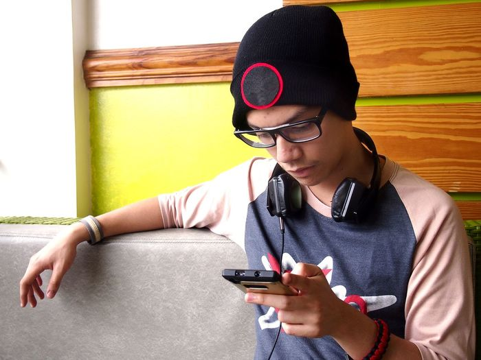 Hipster teen wearing beanie, eyeglasses and headphones using a smartphone Boy Call Cellphone Communication Electronics  Fashion Gadget Hipster Internet Kid Male Millenial Online  Phone Smartphone SMS Surf Technology Teen Teenager Telecommunication Text Web Young Youth