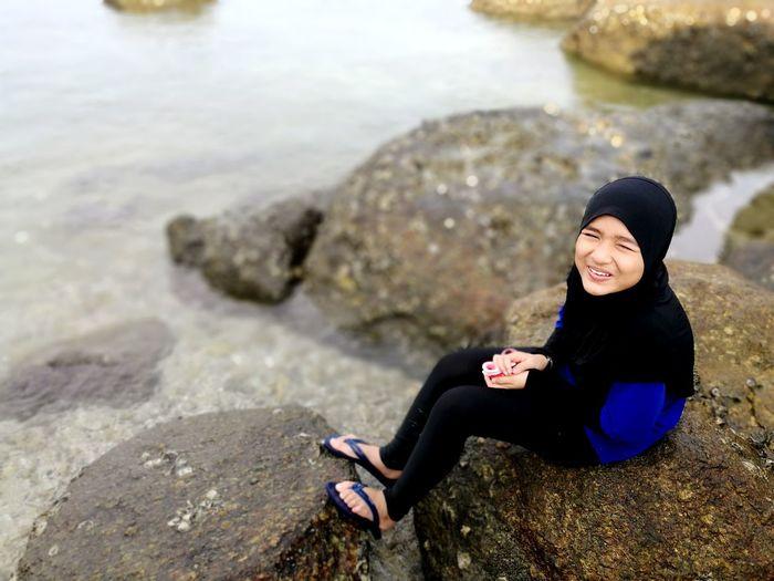 Portrait Of Girl Sitting On Rock By Sea