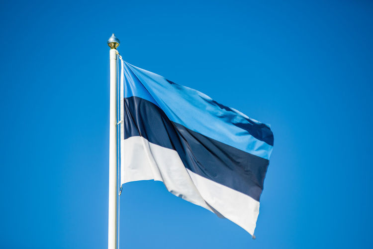 Estonian national flag - black white blue with blue sky and space for text Estonia Blue Clear Sky Copy Space Day Emotion Environment Europe Flag Freedom Independence Low Angle View National Icon Nature No People Outdoors Patriotism Pole Pride Sky Waving Wind