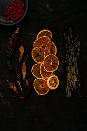 High angle view of dried orange fruits and herbarium on table