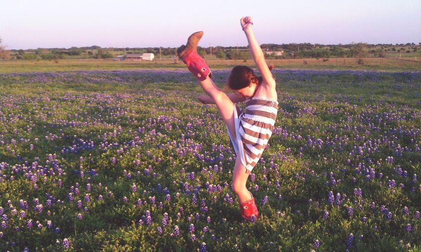 Cheerful Girl Raising Foot Amidst Purple Flowers Blooming On Field