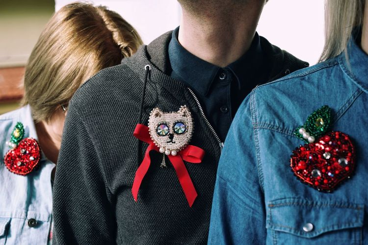 Midsection of friends wearing badges