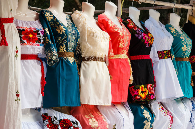 Various clothes hanging in store for sale in market