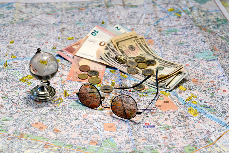 Sunglasses, a glass globe and money on a tourist map background. Tourism concept. Dollar Money Cash Savings Banking Finance Bill Currency Wealth Background Banknote Bussiness Profit Green Close-up USD Exchange Loan  Paper Sign Payment Pay Stack Number Textured  Abstract Earnings Symbol Capital Assets Sunglasses Map Tourism Euro Coins Travel Destination Concept Glass Globe Glass - Material Paper Currency Business No People Indoors  Coin Investment World Map Global Business Planning Large Group Of Objects Choice High Angle View Global Finance Economy