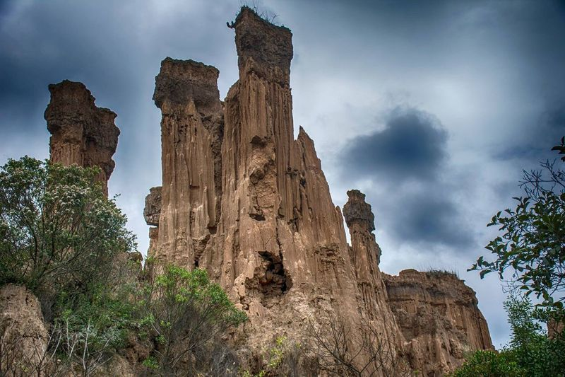 Low angle view of rock formation against cloudy sky