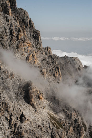 Scenic view of rocky mountains in foggy weather