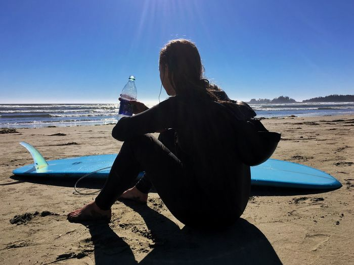 Woman By Surfboard Drinking Water On Beach Against Clear Sky