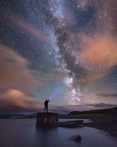 Man standing under star field