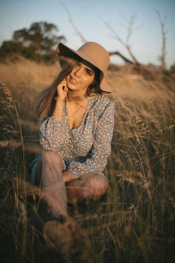 Portrait of young woman wearing hat while sitting on grassy land during sunset