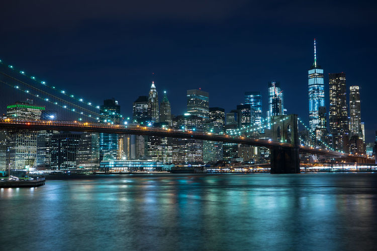 Illuminated Brooklyn Bridge Over River Against Buildings At Night