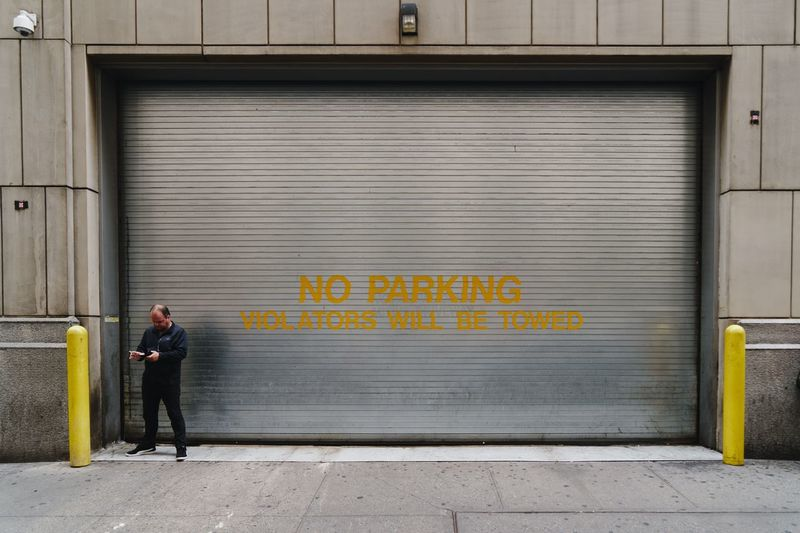 Full Length One Person Architecture Shutter City Communication Building Exterior Closed Text Built Structure Standing Adult Western Script Street Real People Corrugated Iron Day Entrance Wall - Building Feature