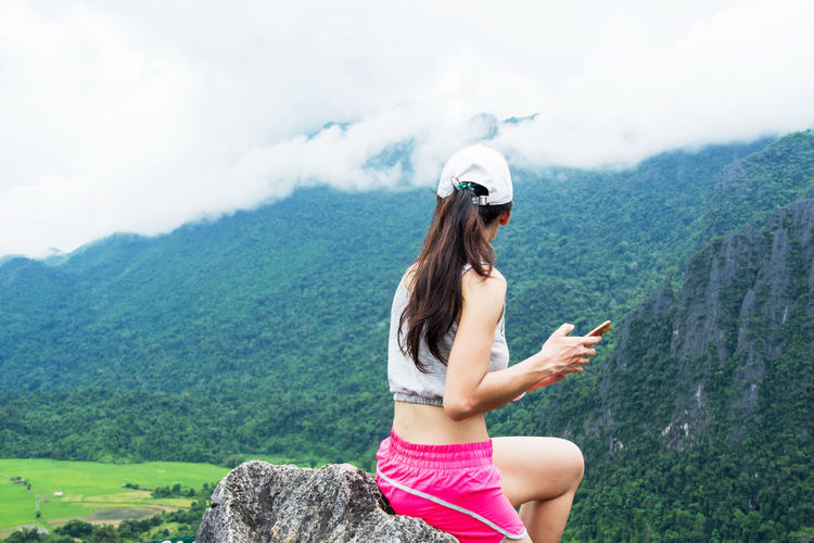 Young woman using mobile phone against mountain