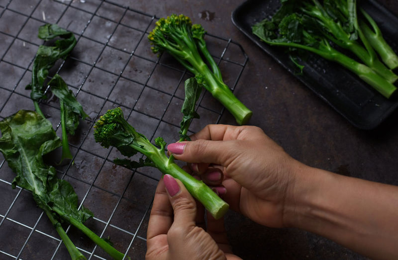 Cropped hands of woman holding vegetables in kitchen