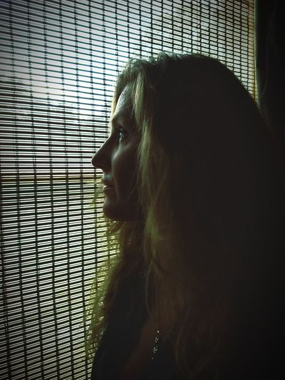 Thoughtful mature woman looking through window at home