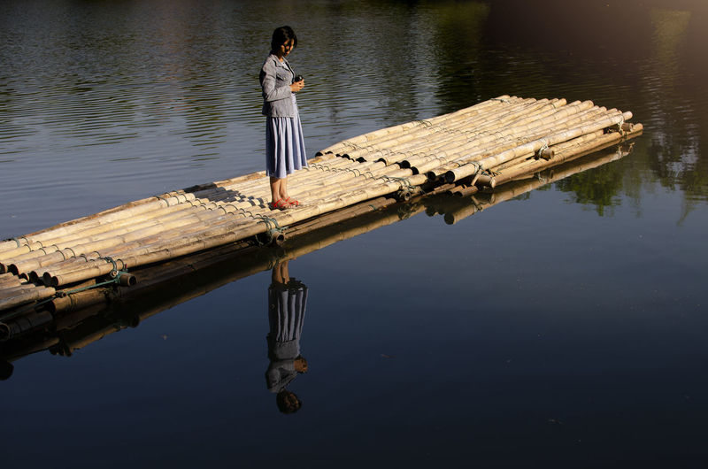 High angle view of woman standing on wooden raft in lake