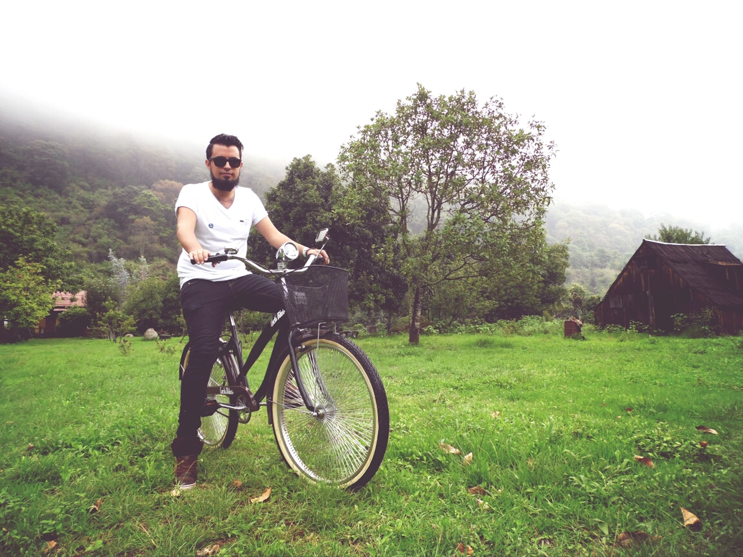 bicycle, full length, lifestyles, grass, land vehicle, transportation, mode of transport, leisure activity, casual clothing, young adult, tree, person, side view, riding, field, young men, standing, day