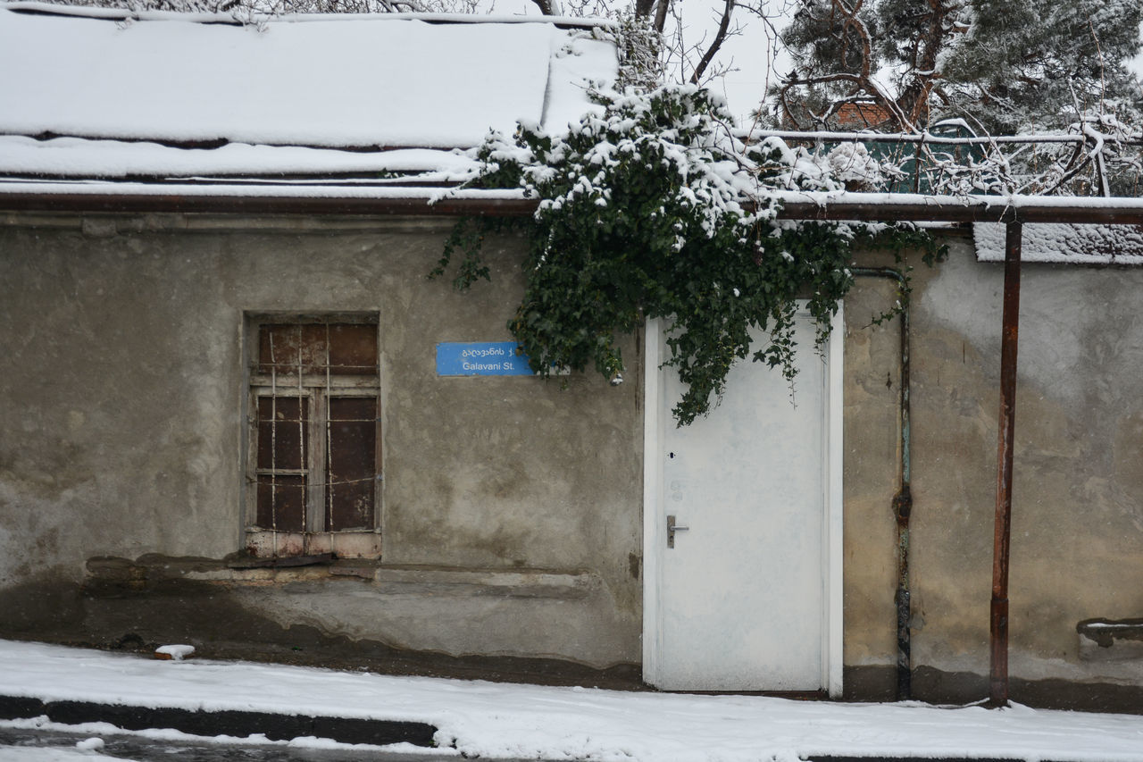 SNOW COVERED HOUSE BY BUILDING