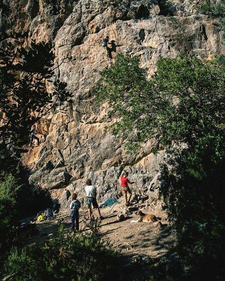 People walking on rocks against mountain range