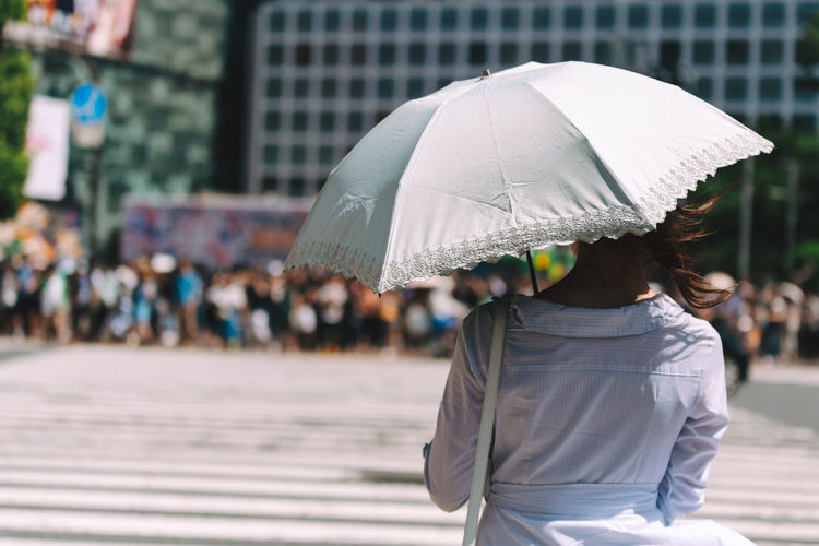 Midsection of woman with umbrella walking in rain