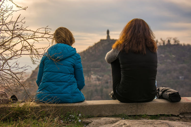 Rear view of female friends sitting on retaining wall against mountain