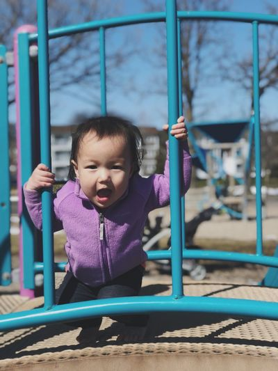 Portrait of baby girl standing on jungle gym at playground