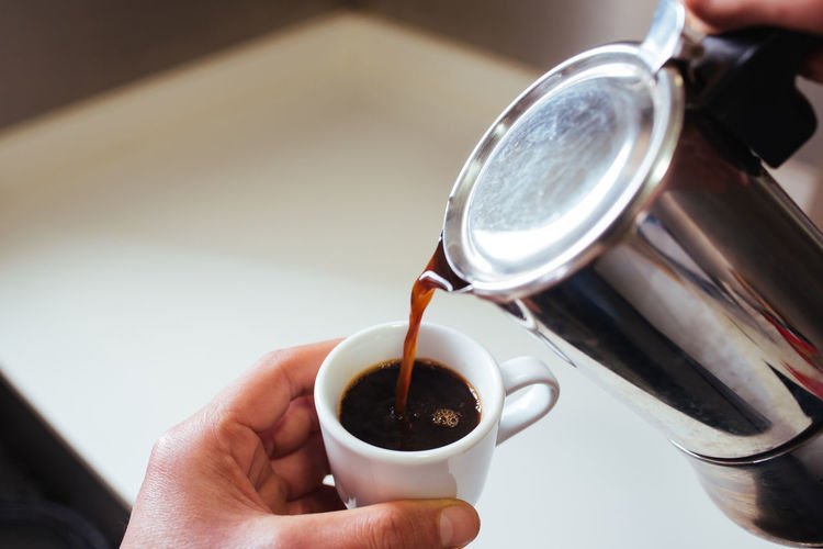 Cropped hand of of person pouring coffee in cup