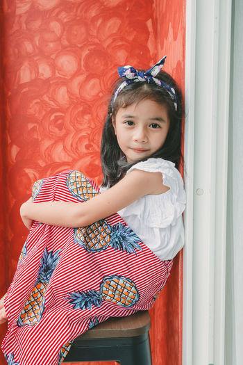 Portrait of cute girl sitting against wall