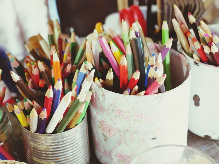Close-Up Of Colorful Pencils In Containers On Table